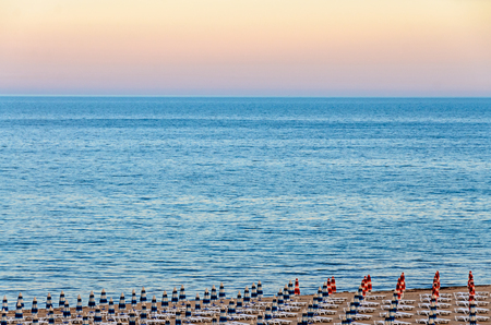 The Black Sea shore from Albena, Bulgaria with golden sands, blue fresh water, sunbeds and umbrellas at sunset.