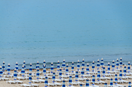 The Black Sea shore from Albena, Bulgaria with golden sands, blue fresh water, sunbeds and umbrellas near beach hotels.