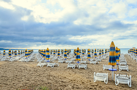 Colored stripped sun umbrellas, golden beach sand and sunbeds, sea water and clouds sky. Stock Photo