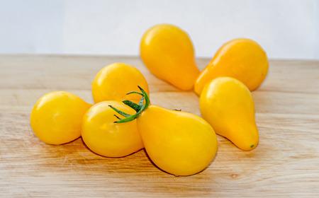 Yellow cherry tomato fruits, plant Solanum lycopersicum, wooden background, close up.