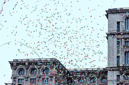 Colored confetti falling, blue sky in a european city, close up background. Stock Photo - 93010938
