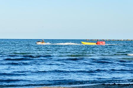 MAMAIA, ROMANIA - SEPTEMBER 15, 2017: Man riding a jet ski over blue Black Sea water, banana boat. Éditoriale