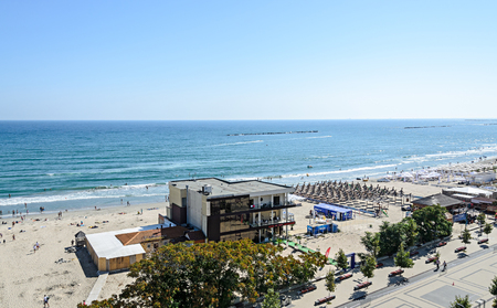 MAMAIA, ROMANIA - SEPTEMBER 15, 2017: Beach of Black Sea with golden sands, sun umbrellas, sunbeds, blue clear water, bars and hotels.