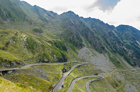 The Transfagarasan road in Fagaras mountains, Carpathians with green grass and rocks, peaks in the clouds.