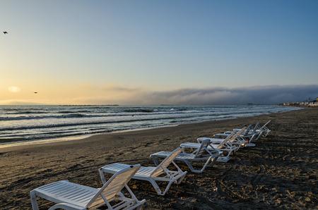 Sunbeds on the beach of Black Sea at sunrise, warm sunshine atmosphere.