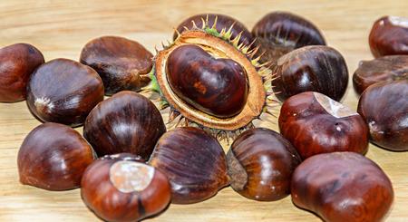 Edible brown chestnuts close up, wooden background. Banco de Imagens