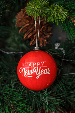Christmas tree hanging ornament, red globe with write happy new year, close up.