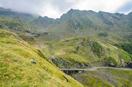 The Transfagarasan road in Fagaras mountains, Carpathians with green grass and rocks, peaks in the clouds. Standard-Bild