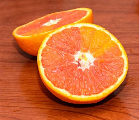 Half orange jucy fruit, close up, wood background.