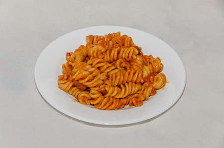 White plate with pasta spaghetti with red tomato sauce,  arrabiata with mushrooms, bacon, parmezan. Banco de Imagens