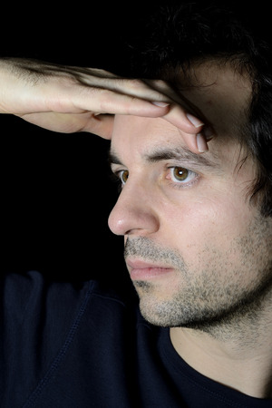 hand on forehead: young man looking away with a hand on the forehead. Black background