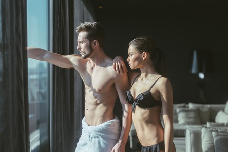 Athletic couple in love looking outside through the window of a luxurious hotel room and daydreaming