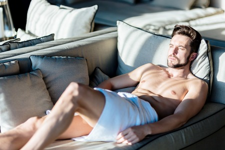 towel wrapped: Squinting young, beautiful man relaxing on a couch in a hotel with a towel wrapped around his hips Stock Photo