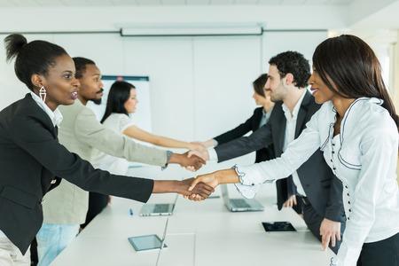 manos estrechadas: La gente de negocios d�ndose la mano antes de sentarse a una mesa de conferencias