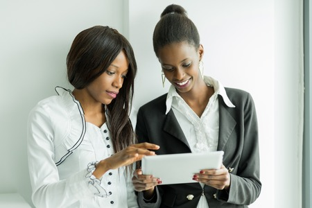 two people meeting: Two colleagues talking while standing about the contents on a tablet pc in a well lit office close to the window Stock Photo