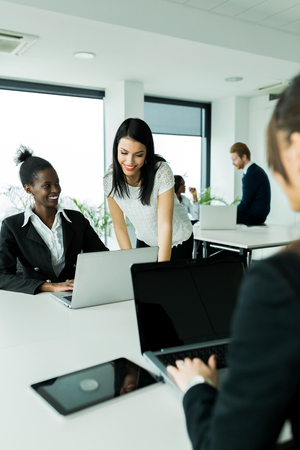 office environment: Black and white businesswomen looking at a laptop and working in a neat office environment
