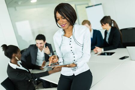 black professional: Beautiful, young, black, african businesswoman using a tablet at an office meeting Stock Photo