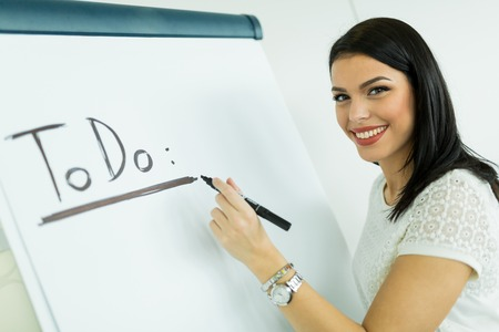 writing board: Beautiful, young, businesswoman writing todo onto a white writing board