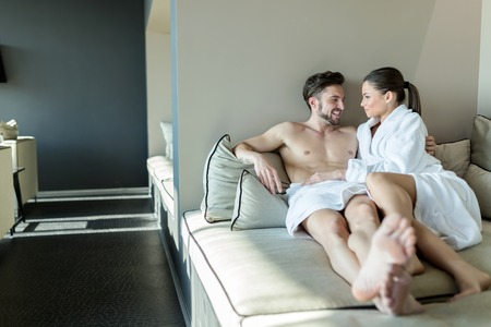 woman bathrobe: Lovely couple relaxing at a wellness center, laying in a rob and towel