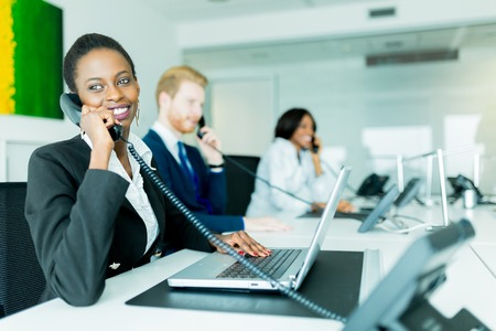 A beautiful, black, young woman working at a call center in an office with her red haird partner on the other end of the desk talking to another customer Stockfoto