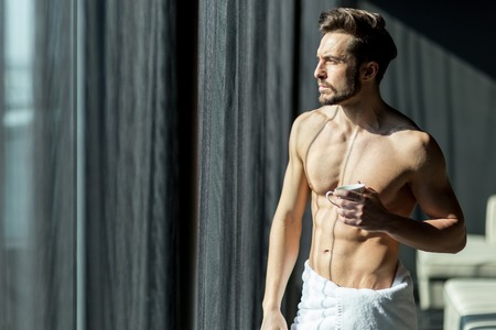 shirtless man: Handsome, muscular, young man drinking his morning coffee in a hotel room standing next to a window and looking against bright sunlight with towel wrapped around his waist Stock Photo
