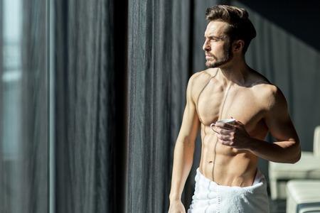 toallas: Hombre joven y musculoso, bebiendo su café de la mañana en una habitación de hotel de pie junto a una ventana y mirando contra la luz brillante del sol con una toalla envuelta alrededor de su cintura