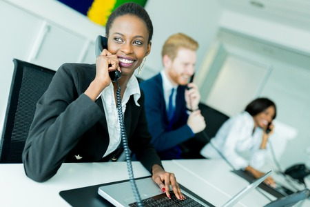 black person: A beautiful, black, young woman working at a call center in an office with her red haird partner on the other end of the desk talking to another customer Stock Photo