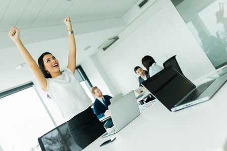 Businesswoman jumping from joy and raises both hands as a sign of success Stock Photo