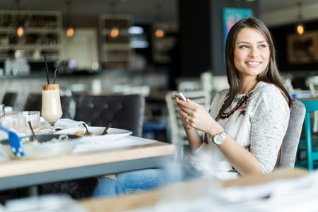 バーに座って、携帯電話を押しながら笑顔の美しい女性 写真素材