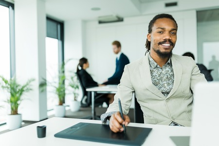 office environment: Black handsome graphics designer  with dreadlocks using digitizer in a well lit, tidy office environment  while his colleagues are working overtime in the background Stock Photo