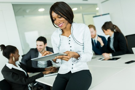 woman think: Beautiful, young, black, african businesswoman using a tablet at an office meeting Stock Photo