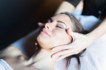 マッサージ師はマッサージ テーブルの上に横たわる美しい、若い女性の顔の治療