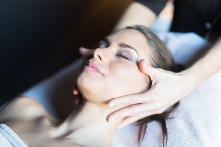 Masseur treating face of a beautiful, young woman lying on the massage table Banque d'images