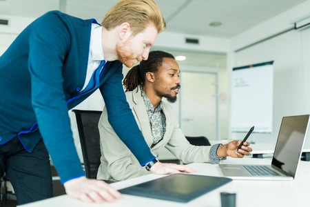 flaws: A black young man with dreadlocks and a young handsome red haired businessman discussing graphics design flaws in a nice white office