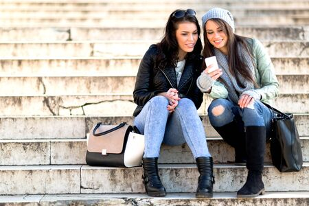 telephone: Two youngand beautiful women sitting at the stairs and taking a selfie Stock Photo