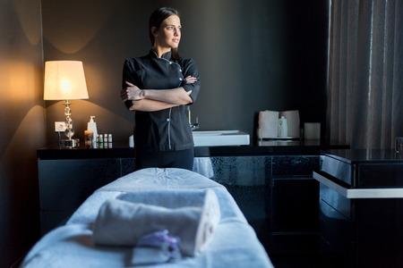 spas: Massage Therapeutin stehend durch bassage tavle mit gekreuzten Händen und Blick aus dem Fenster