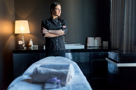 Massage therapist standing by bassage tavle with hands crossed and looking outside the window