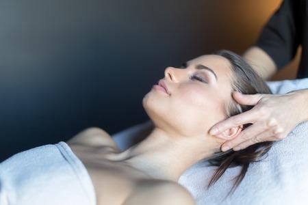 Masseur behandelen gezicht van een mooie, jonge vrouw liggend op de massagetafel