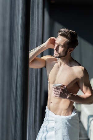 towel wrapped: Handsome, muscular, young man drinking his morning coffee in a hotel room standing next to a window and looking against bright sunlight with towel wrapped around his waist Stock Photo