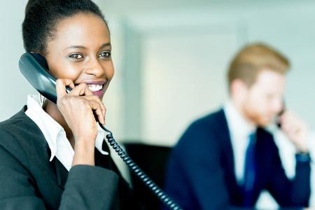 gente comunicandose: Un hermoso negro, mujer, joven que trabaja en un centro de llamadas en una oficina con su pareja haird rojo en el otro extremo de la mesa hablando con otro cliente Foto de archivo