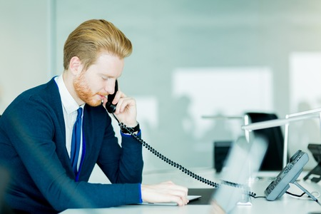 Een knappe man, roodharige arbeider in een call center office praten over een telefoon