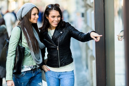 showwindow: Two young and beautiful women pointing at a show-window