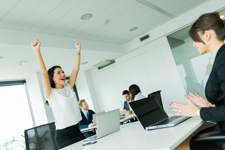 raises: Businesswoman jumping from joy and raises both hands as a sign of success Stock Photo