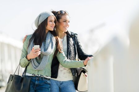 looking over: Two young and beautiful women looking over a dock fence