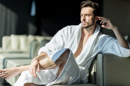 ローブのホテルの部屋に座って朝思考で若く、ハンサムな男