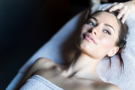 therapy room: Portrait of a beautiful, young womanwhile lying on a massage table