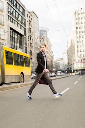 shure: Businessman rushing accross the road in a hurry Stock Photo