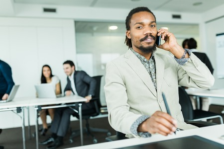 working overtime: Black handsome graphics designer  with dreadlocks using digitizer in a well lit, tidy office environment and talking on the phone while his colleagues are working overtime in the background