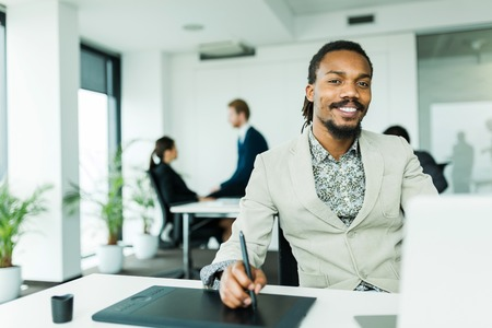 working overtime: Black handsome graphics designer  with dreadlocks using digitizer in a well lit, tidy office environment  while his colleagues are working overtime in the background Stock Photo