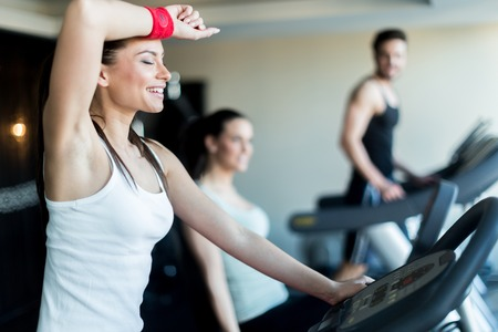 Young, beautiful woman training by riding a bicycle in a gym and sweating